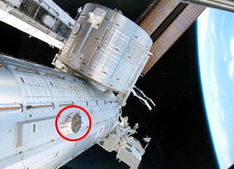 The red circle on the photo indicates a PDGF attached to the Japanese Experiment Module