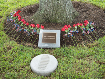 Roses laid at the foot of the tree and a replica of Neil's first footstep on the moon.