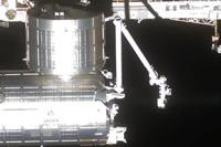 写真:ISSに取付けられた「きぼう」とロボットアーム(中央)