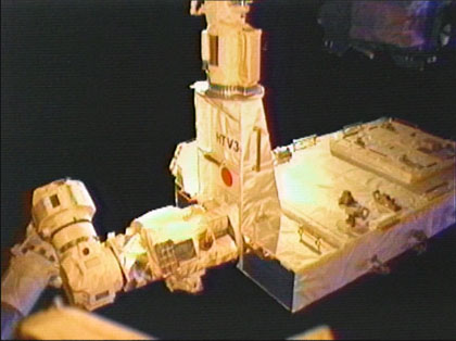 画像:「きぼう」ロボットアーム(上)からISSのロボットアーム(左)に受け渡される曝露パレット
