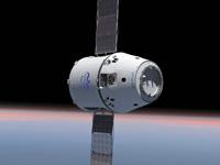 軌道上を飛行するドラゴン補給船のイメージ