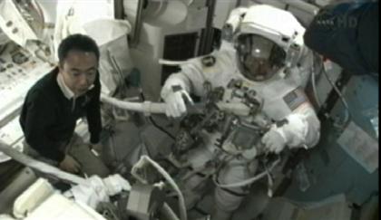 写真:EMUの装着を支援する古川宇宙飛行士
