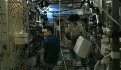写真:ドラゴン補給船運用1号機で回収する実験サンプルを、MELFIからGLACIERに移す作業を行うウィリアムズ、星出両宇宙飛行士