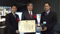 記念品と表彰状を手にする関係者(左から松村技術領域リーダ、桑尾氏(NEC)、土井主任開発員)
