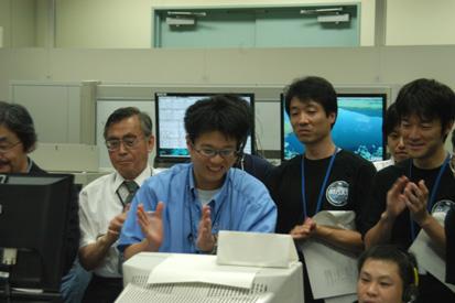 ユーザ運用エリアで初回起動の様子をモニタする研究グループ 左手奥が代表研究者の松岡勝 理化学研究所 名誉研究員