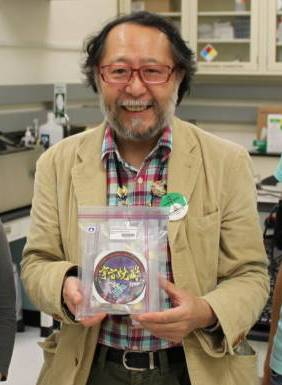 Professor Hideyuki Majima, holding returned onboard items.