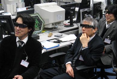 写真:実験運用管制室で実施の様子を見守るCIの川邊氏、PIの村山教授、CIの渡邊氏(左から)(3D用画面を見るため、専用メガネをかけている)