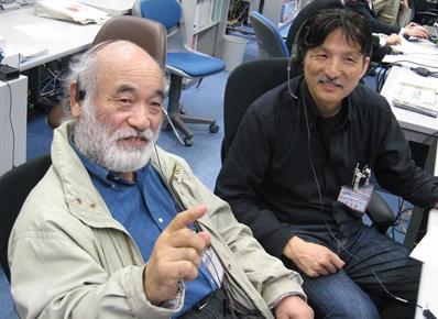 写真:実験運用管制室で実施の様子を見守るPIの福嶋先生(左)とCI(共同提案者)の今西先生(右)