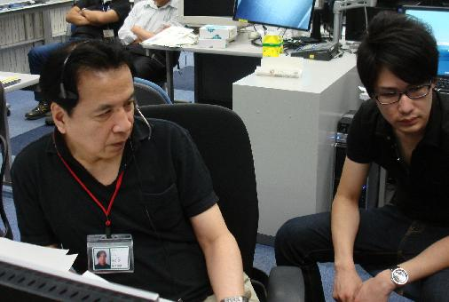 Prof. Tsukamoto (left) monitors the experiment proceeding from the User Operations Area (UOA) at the Tsukuba Space Center (TKSC) (Credit: JAXA)