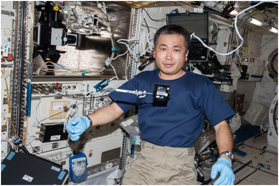 In front of the Fluorescence Microscope (upper left) installed on Kibo, Astronaut Wakata poses for a photo before setting the sample chamber (floating below his face).