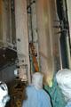 棒状の道具を使ったラジエターホースの収納作業