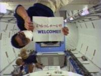 船内実験室へ入室直後の星出宇宙飛行士。手持ちの紙には「いらっしゃ~い!!WELCOME」の文字