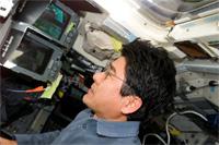 エンデバー号のフライトデッキで作業をする土井宇宙飛行士