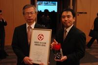 「グッドデザイン賞(金賞)」記念品を手にする白木理事(左)と筒井計画マネージャ(右)