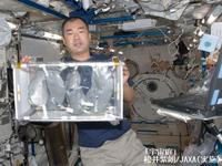 宇宙庭の栽培キットを持つ野口宇宙飛行士(©松井紫朗/JAXA(実施))