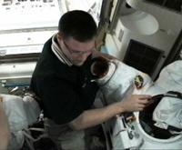 船外活動ユニット(EMU)の準備を行うウィーロック宇宙飛行士(出典:JAXA/NASA)
