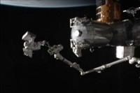 SSRMSの先端に乗ってMBSUを運ぶ星出宇宙飛行士(出典:JAXA/NASA)